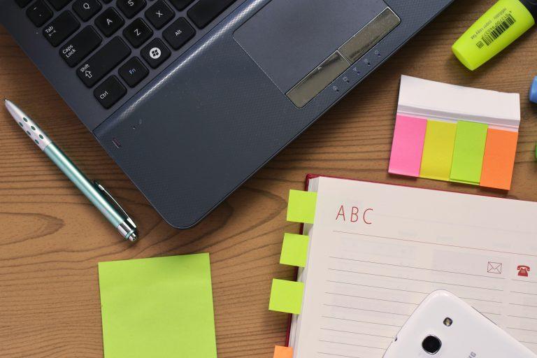 Foto de uma mesa com um notebook, uma agenda com post-its, uma caneta, um celular, um bloquinho post-it verde limão, vários marcadores post-it coloridos e uma caneta marcadora também verde-limão.