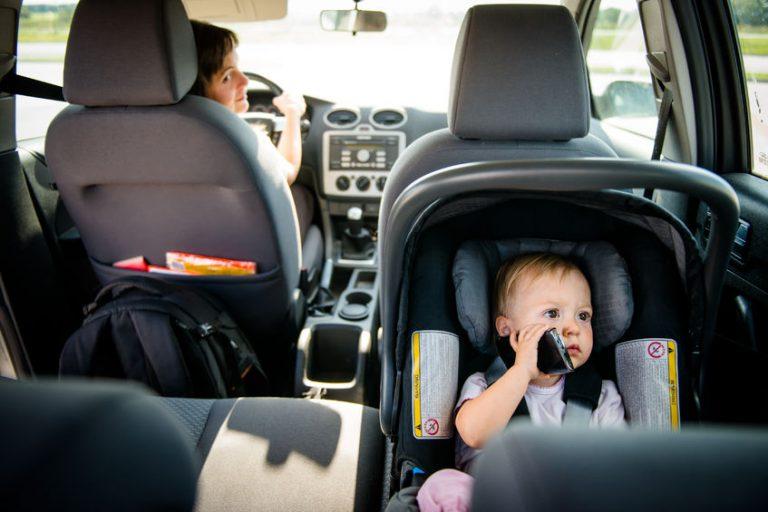 Um carro com uma mulher dirigindo. No banco de trás existe um bebê em uma cadeirinha infantil.