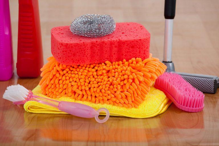 Uma escova, uma toalha, um rodo esfregão, uma esponja e uma palha de aço.