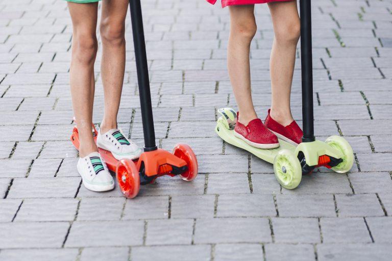 magem das pernas de duas meninas, cada uma com os pés em cima de um patinete