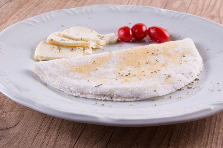 Foto de uma tapioca ao lado de três tomatinhos cereja e fatias de manteiga, em cima de um prato branco.