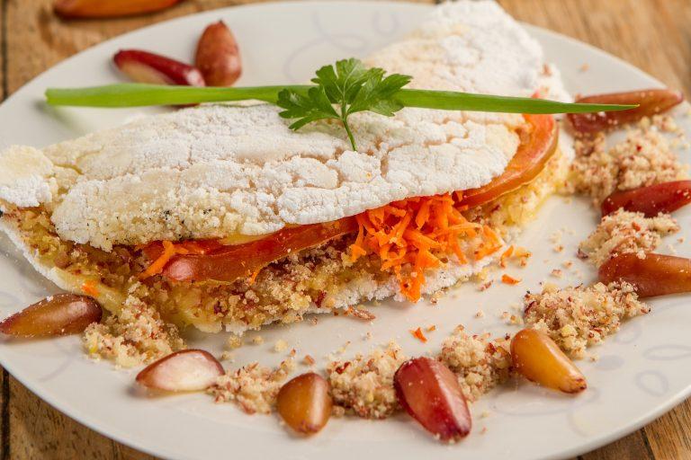 Foto de uma tapioca recheada com tomate, cenoura ralada e farofa de algum grão. O prato branco está decorado com grãos e a mesma farofa.
