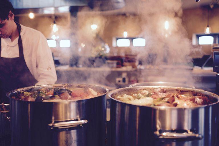 Foto que mostra, em primeiro plano, duas grandes panelas industriais de inox, com alimentos cozinhando até a boda e fumaça saindo. Em segundo plano, na lateral esquerda, um homem olhando pra baixo, vestindo avental escuro e camisa social branca.