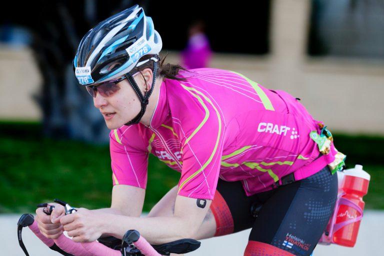 Mulher com roupa de ciclista pedalando.