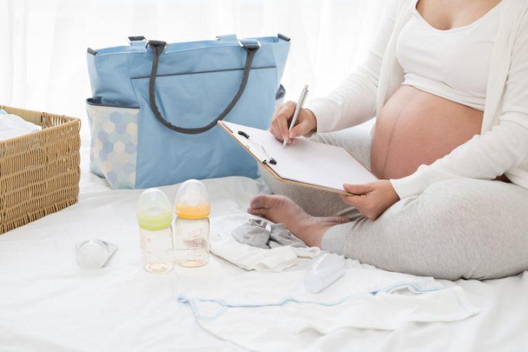 Gestante sentada arrumando bolsa com checklist na mão.
