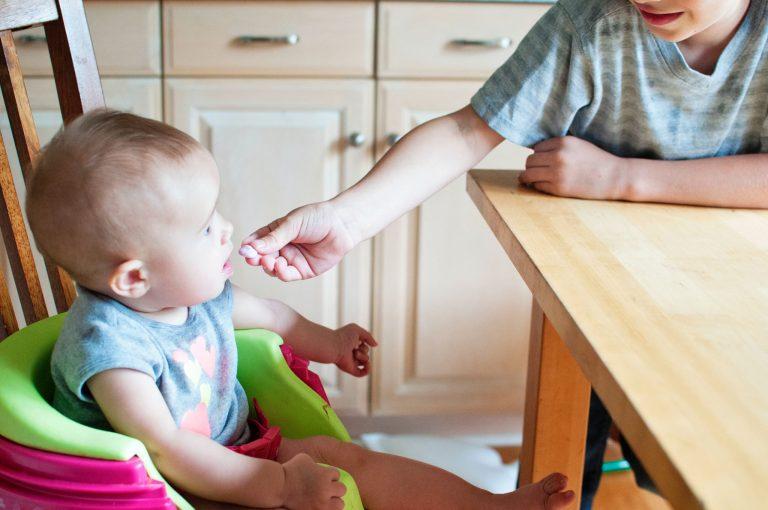 Imagem de uma criança sentada em uma cadeira de alimentação.