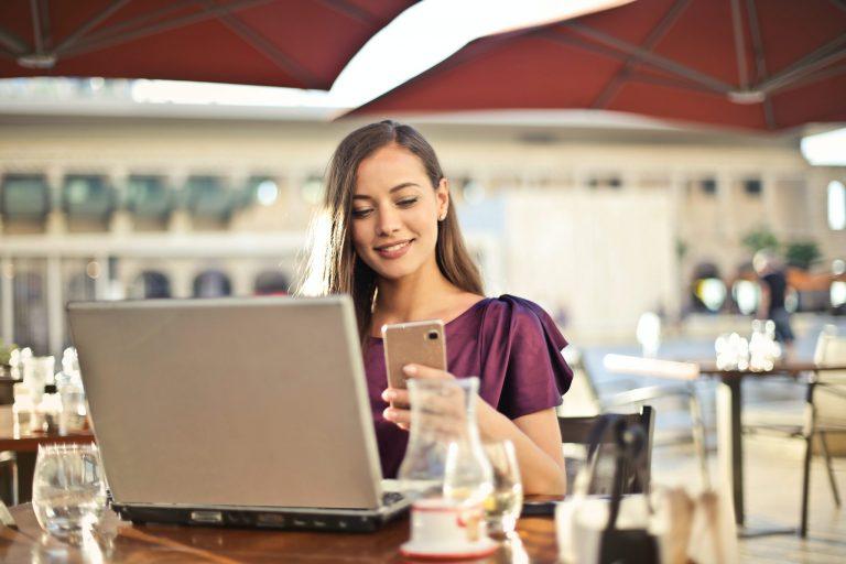 Mulher usando celular com notebook aberto.