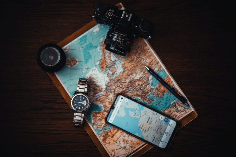 Mapa, câmera fotográfica e celular.