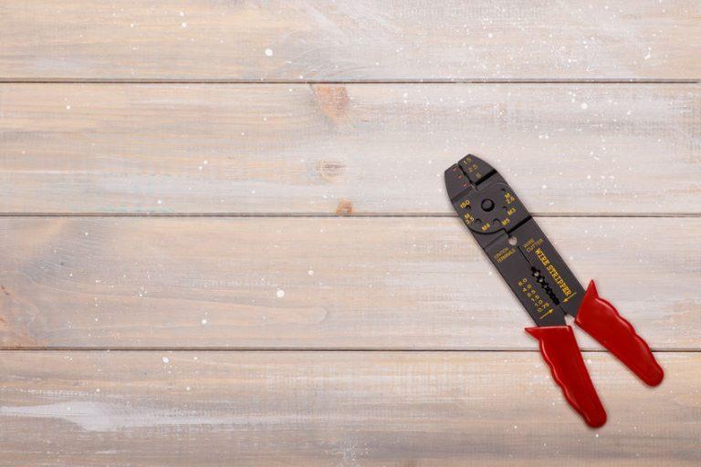 Um alicate desencapador multifuncional em cima de uma superfície de madeira.