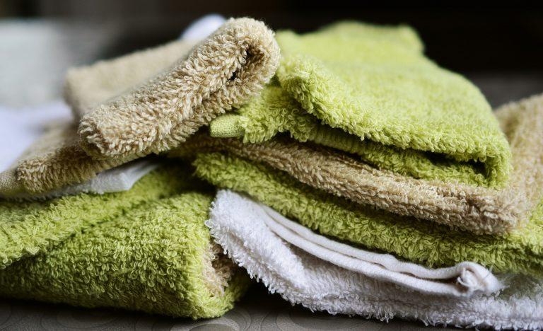 Imagem de toalhas de banho brancas, verdes e marrons empilhadas