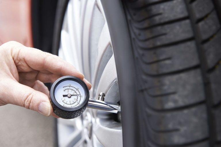 Um calibrador encostado no bico de ar de um pneu.