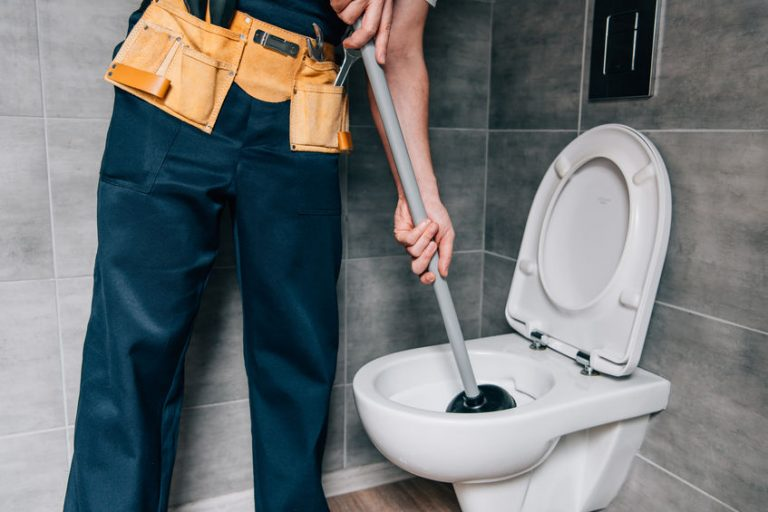 Um encanador usando um desentupidor de cabo longo para desentupir um vaso sanitário.