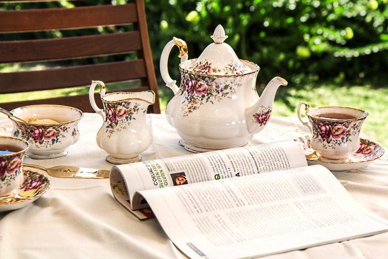 Imagem de jogo de chá clássico sobre mesa com toalha branca e revista aberta