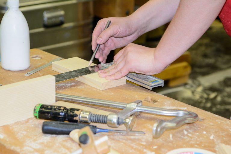 Em uma mesa de carpinteiro uma mão masculina usa um lápis de carpinteiro, enquanto a outra mão do mesmo homem segura um pedaço de madeira.