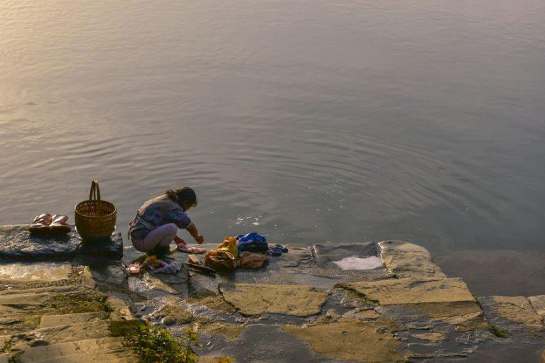 Imagem de mulheres lavando roupa no rio utilizando lava roupas líquido