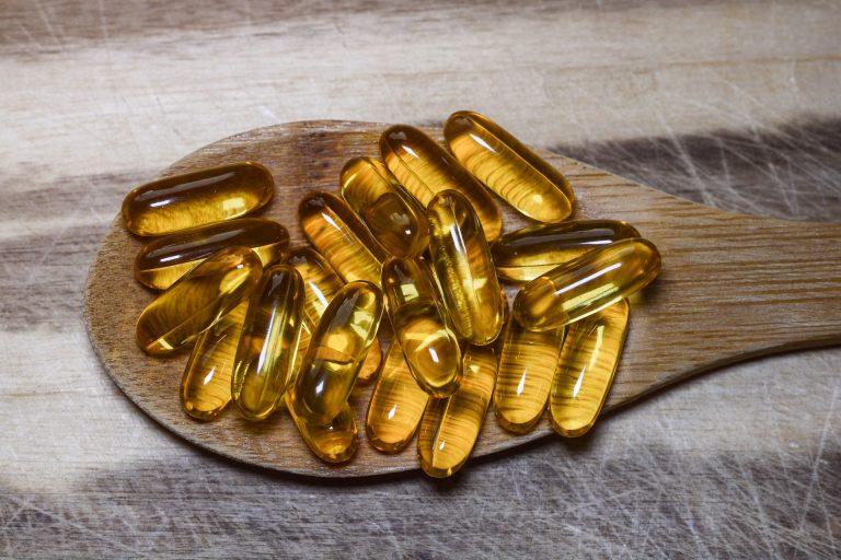 Imagem de capsulas gelatinosas em uma colher de madeira.