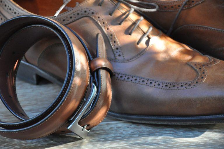 Imagem de cinto masculino de couro marrom ao lado de par de sapato