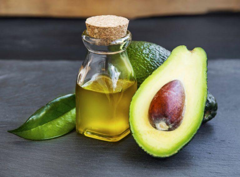 Imagem de abacate cortado com fruta inteira ao fundo e óleo de abacate em frasco de vidro