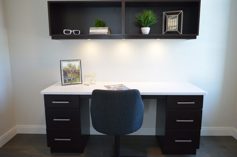 Imagem de bancada de trabalho e nicho com porta-retratos, livros, óculos e plantas