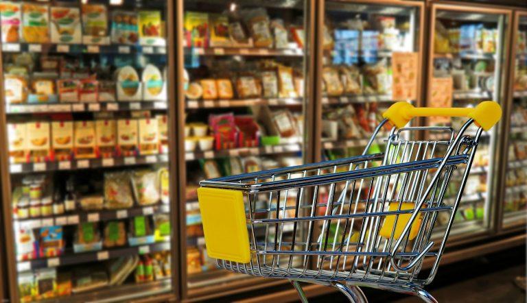 Imagem de carrinho de compra de metal com detalhes em plástico amarelo na frente de geladeiras em supermercado