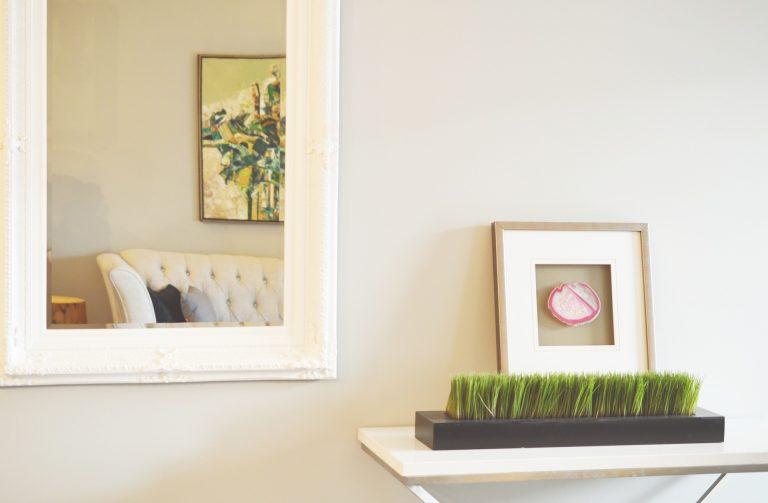 Imagem de porta-retratos de madeira sobre bancada com vaso e espelho pendurado na parede