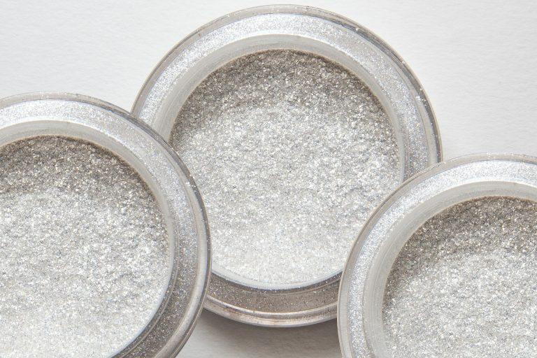 Imagem de três embalagens com glitter em pó