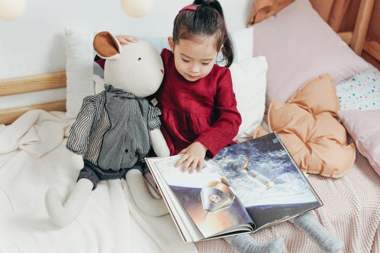 Imagem de uma menina lendo um livro.