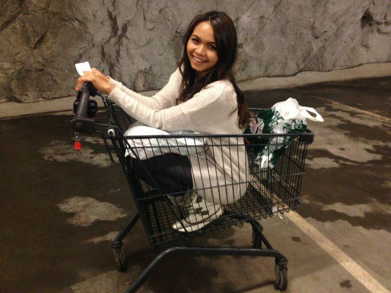 Imagem de mulher de cócoras dentro de um carrinho de supermercado em estacionamento