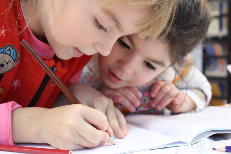 Imagem de duas crianças estudando.