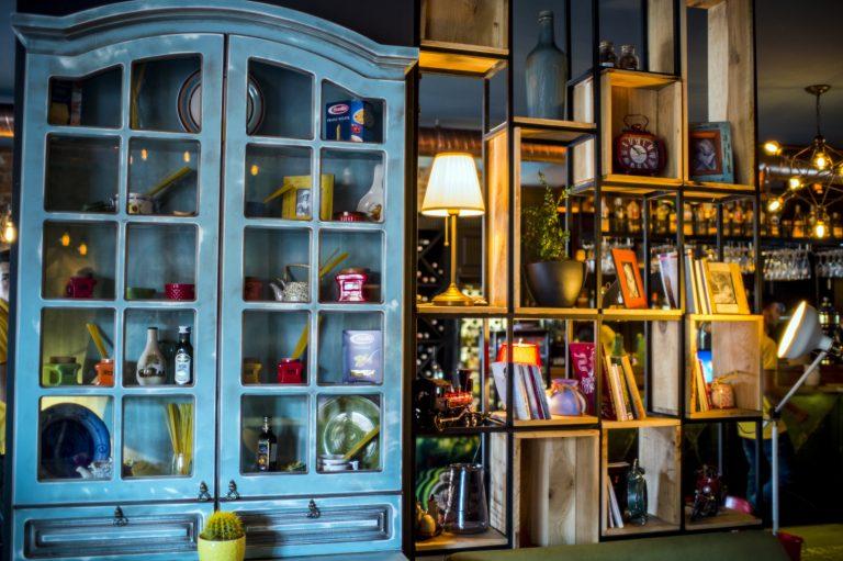 Imagem de porta-retratos espalhados por bancada modular de madeira e ferro ao lado de um armário de madeira azul
