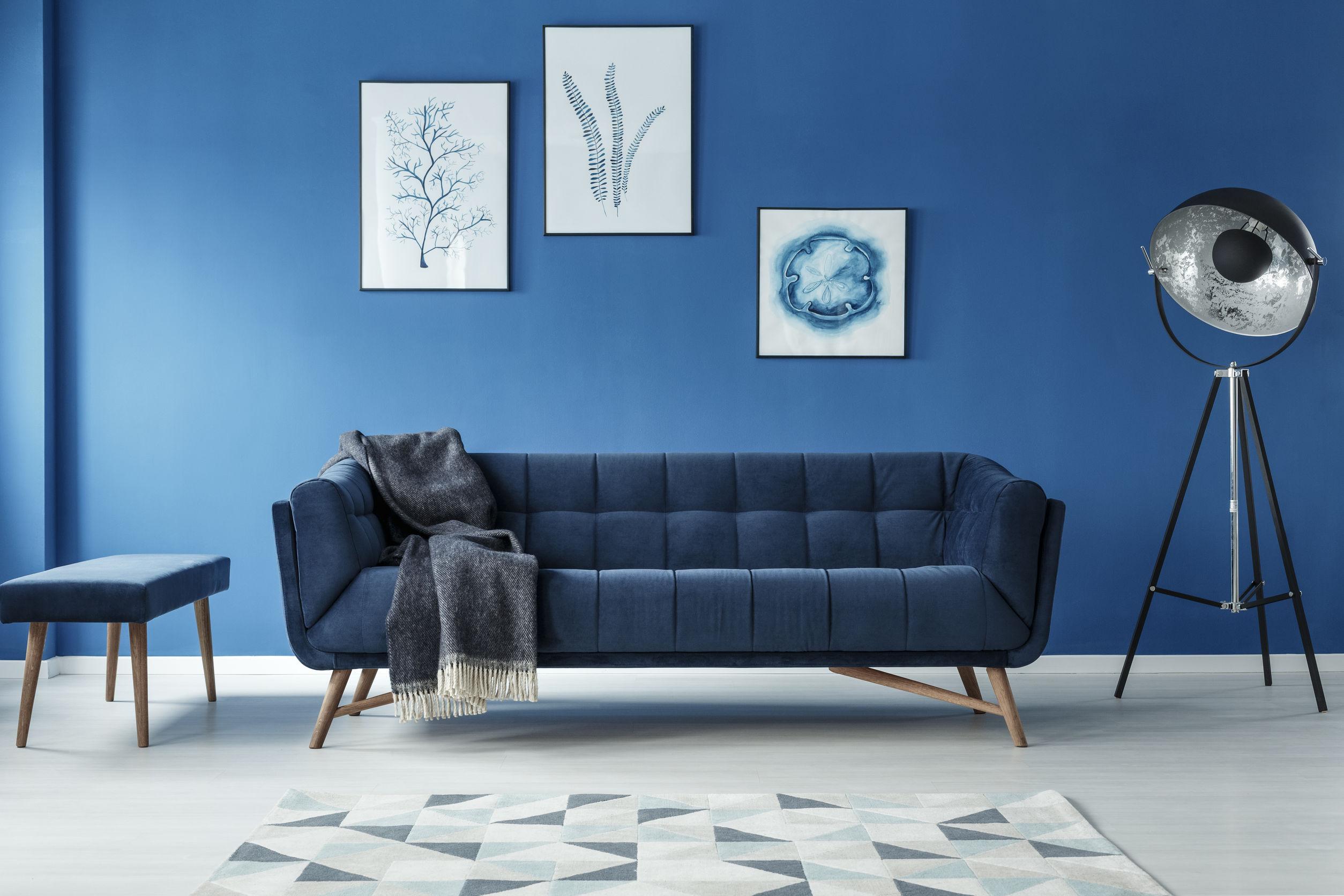 Foto de um sofá de três lugares, com estofado azul, enconstado em uma parede de tijolos branca.