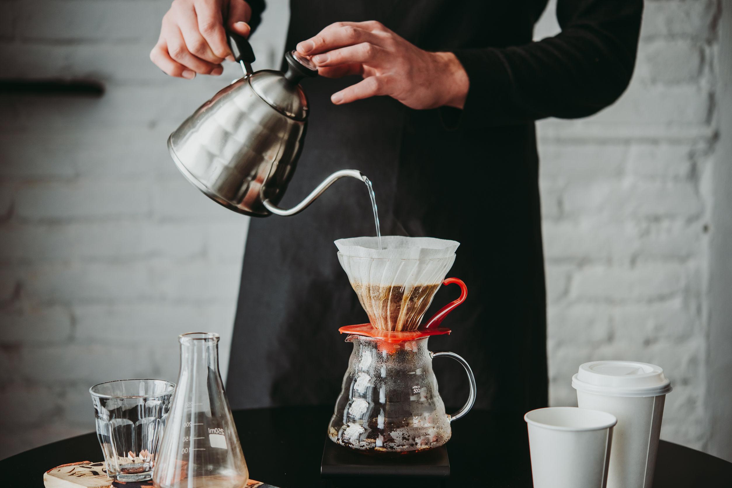 Foto que mostra da cintura pra baixo de uma pessoa preparando café de avental preto, utilizando um conjunto v60.