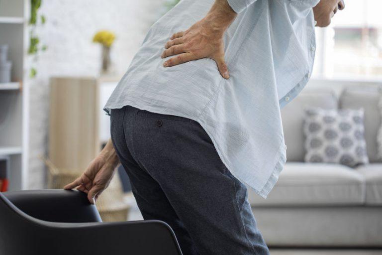 Foto em preto e branco de um homem de meia idade, de costas, com a mão na coluna, como quem sente dor.