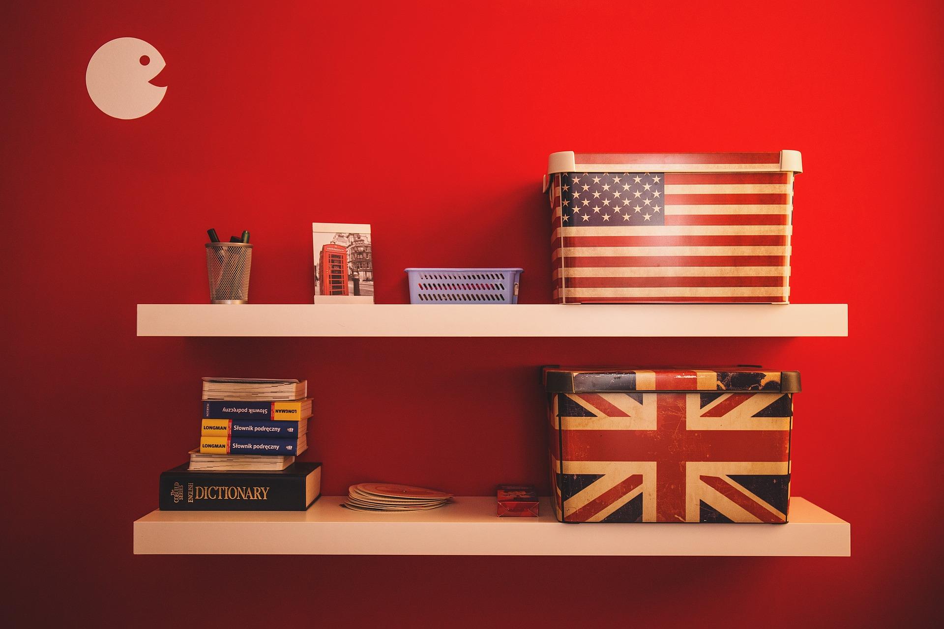 Foto de duas prateleiras brancas em uma parede vermelha com livros, uma foto, canetas, uma caixa organizadora pequena e duas grandes, sendo que uma dessas possui a bandeira da Inglaterra e a outra a bandeira dos Estados Unidos.
