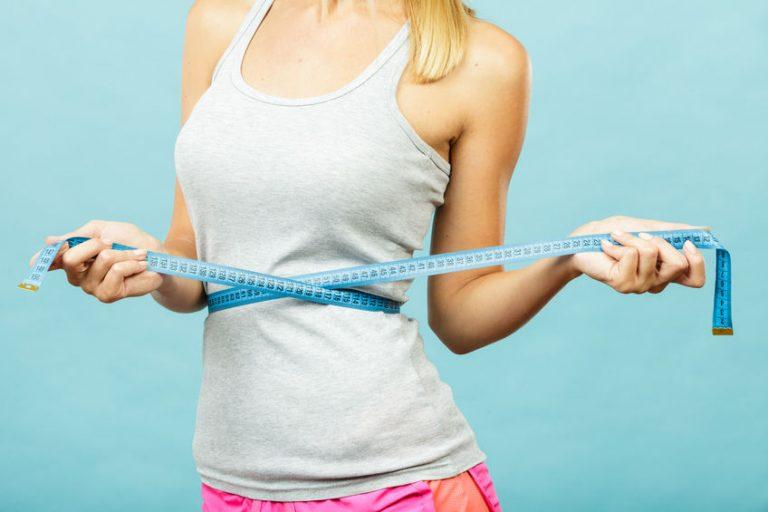 Foto em preto e branco da barriga de uma mulher, que passa uma fita métrica ao seu redor do seu abdômen, tirando sua própria medida