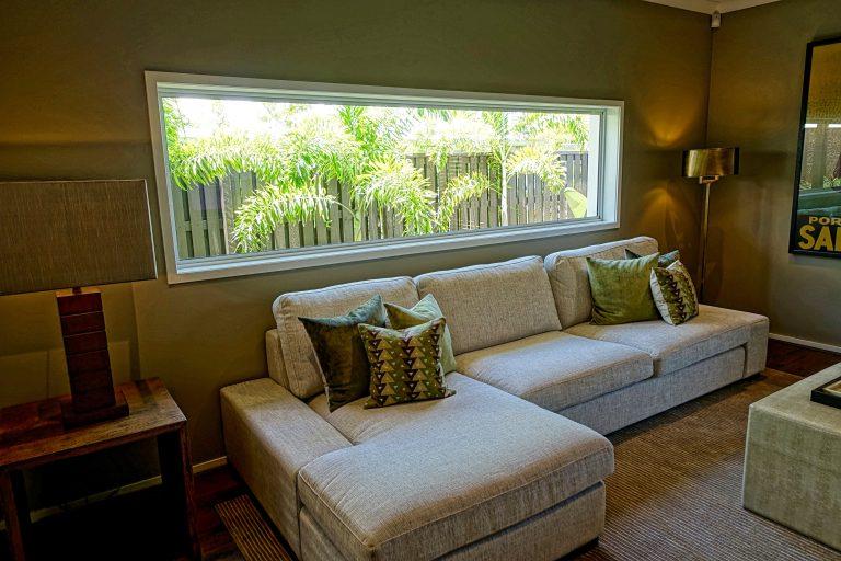 Foto de um sofá com chaise cinza, com almofadas em tons de verde, em uma sala que segue a mesma paleta de cores. Na parede do fundo, uma grande janela horizontal mostra folhas de arbustos.