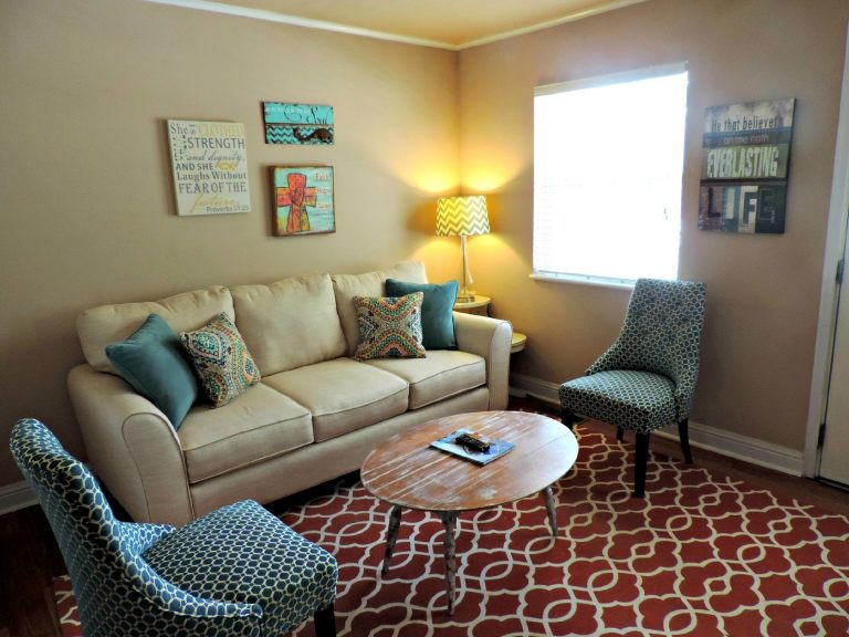 Foto de uma sala com um sofá bege, almofadas coloridas, duas poltronas com estampa predominantemente azul, uma mesa de centro oval, quadro na parede, abajur, tapete e janela lateral com persiana.