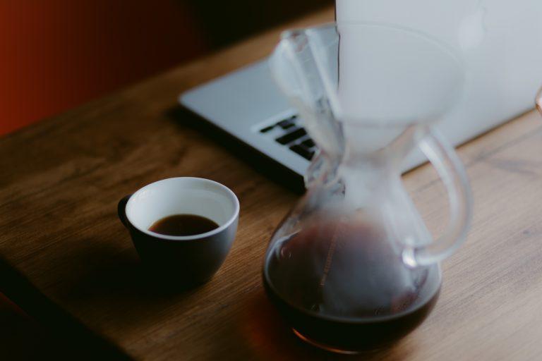 Foto que mostra uma mesa de madeira com uma jarra de vidro com café, ao lado de uma xícara preta e branca também com café, e um notebook ao fundo.