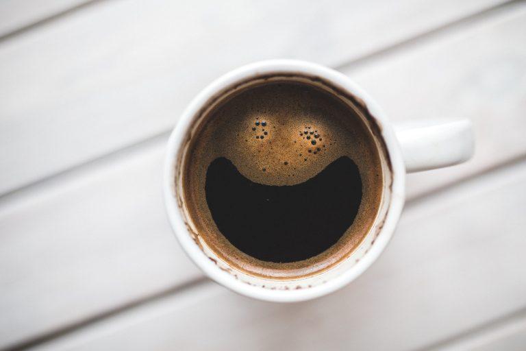 Foto tirada de cima de uma xícara branca de café, com café em seu interior fazendo, sem querer, o formato de uma carinha sorridente.
