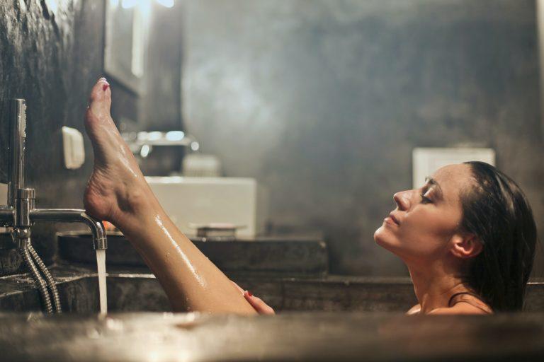 Foto de uma mulher em uma banheira, com uma das pernas para o alto, cabelo molhado e expressão facial de relaxamento. A torneira está aberta e o banheiro tem design escuro e industrial.