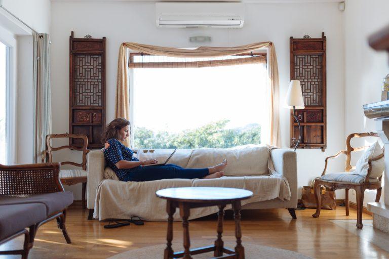 Foto de uma sala, com uma mulher sentada de lado, com as pernas esticadas em um sofá bege. Ainda na sala há alguns móveis de madeira, como mesa de centro, poltronas e estantes. Ao fundo, uma grande janela com cortina de tecido aberta.