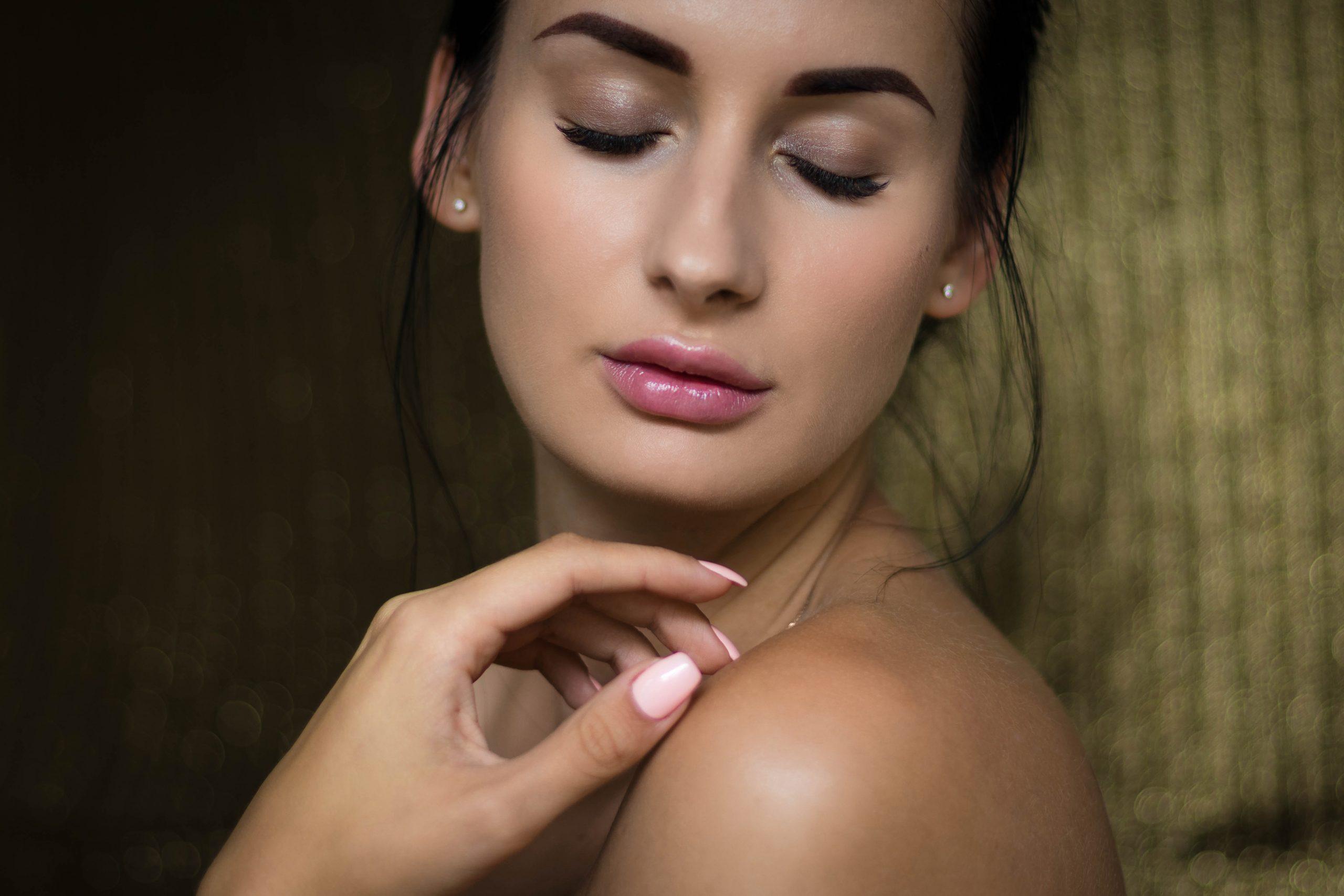 Foto de uma mulher com o rosto de lado, virado para câmera, olhos fechados, cabelo preso e pele limpa. Uma de suas mãos está no ombro.