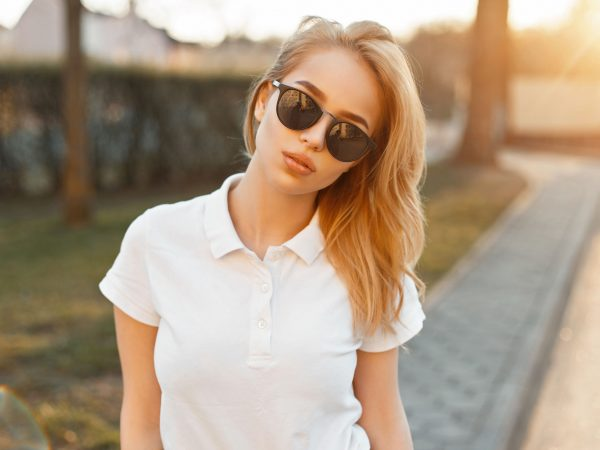 Mulher loira de óculos escuros preto e camisa polo branca. Ao fundo, o reflexo do sol.