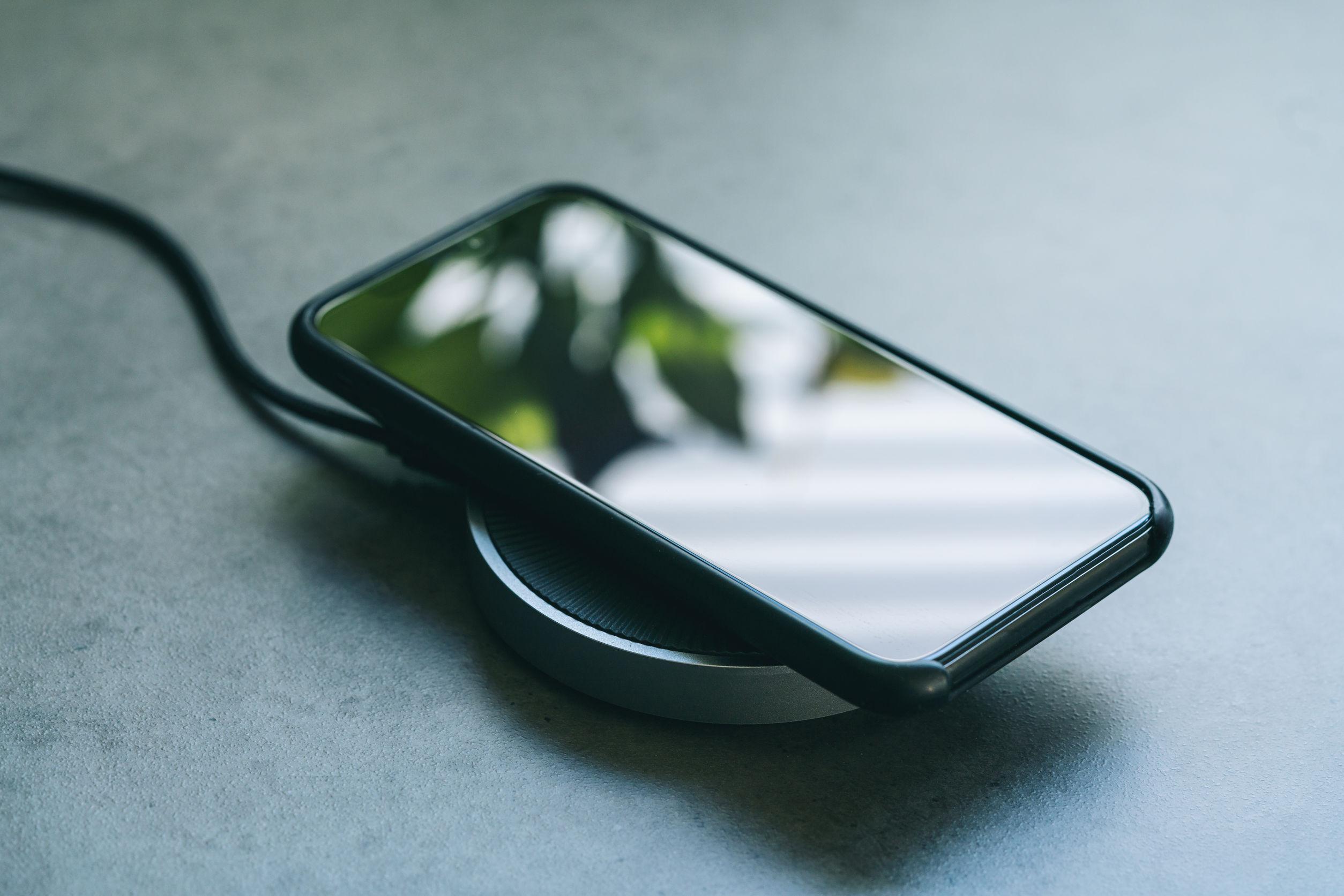 Foto de um celular preto e touch screen, sendo carregado em um carregador por indução.