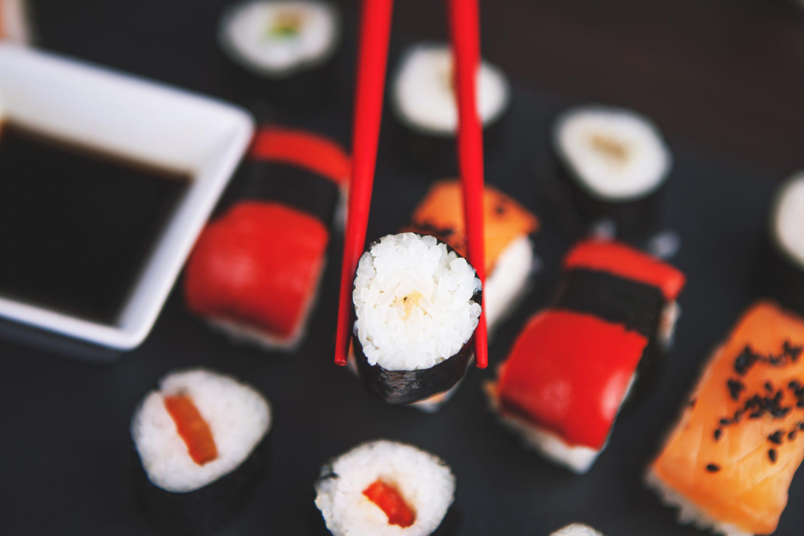 Foto de um hashi vermelho segurando uma peça de makimono, com diversas peças junto com um porta shoyu ao fundo, em blur.