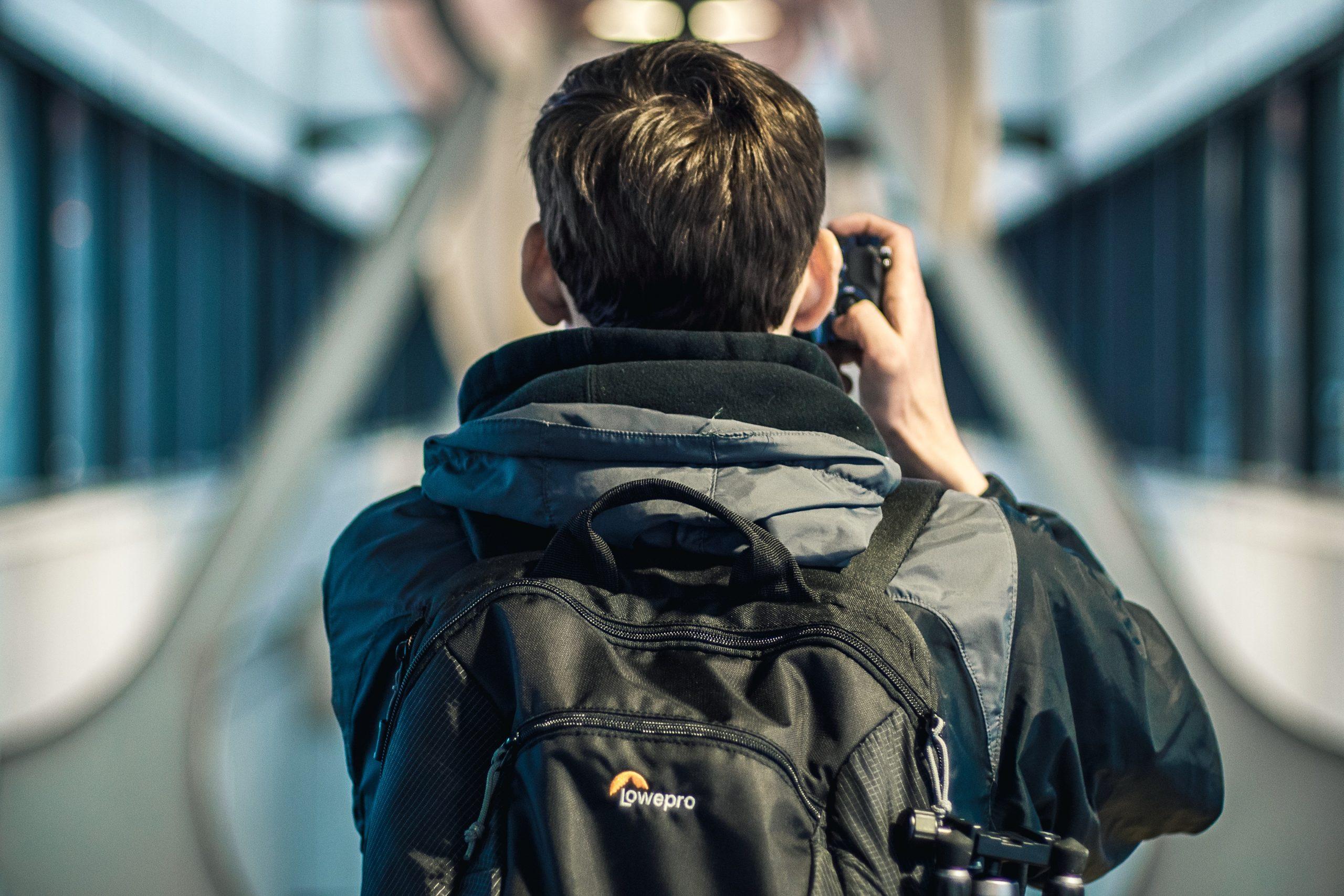 Foto de um rapaz de costas fotografando algo. Ele veste roupas de frio e carrega nas costas uma mochila para fotógrafo preta.