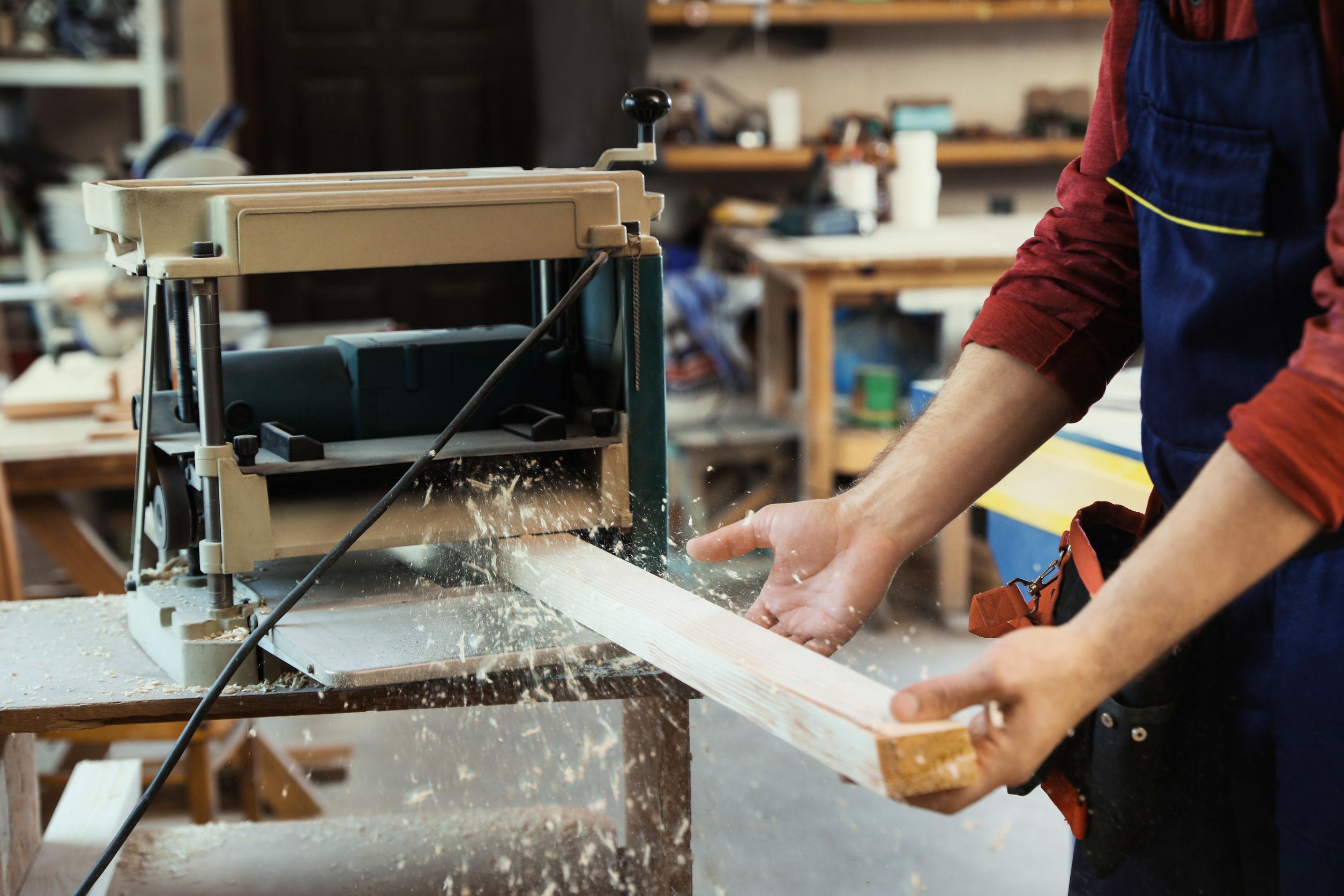 Imagem mostra uma pessoa colocando uma peça de madeira em uma desengrossadeira.