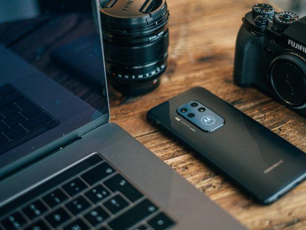 Celular motorola ao lado de notebook e câmera.