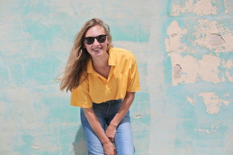 Foto de uma mulher loira, com cabelos esvoaçantes, levemente inclinada para frente e encostada em uma parede, vestindo jeans, camisa polo amarela e óculos de sol.