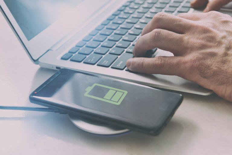 Foto que mostra um carregador opr indução carregando um aparelho celular, ao lado de um notebook sendo usado por mãos masculinas.